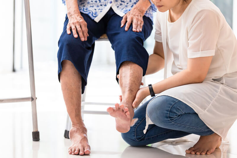 imagen destacada del artículo sobre consejos para el cuidado del pie en las personas mayores donde se ve a una cuidadora sosteniendo el pie de una anciana